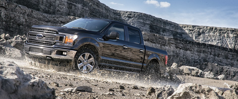 2018 Ford F-150 XLT driving on a rocky road