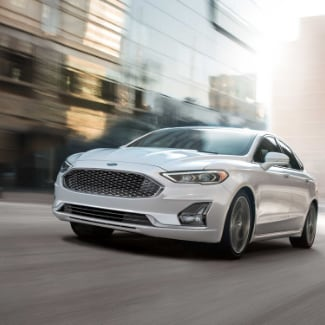 A white 2019 Ford Fusion driving down an empty city street with a blurred view of a building in the background