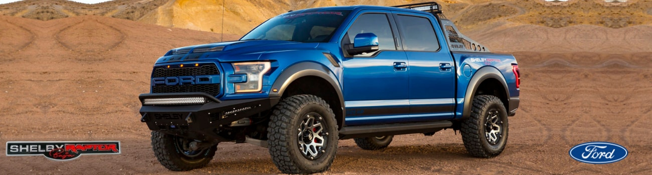 A blue 2018 Shelby Baja Raptor parked in some dirt and sand in a desert scene with off-road hills