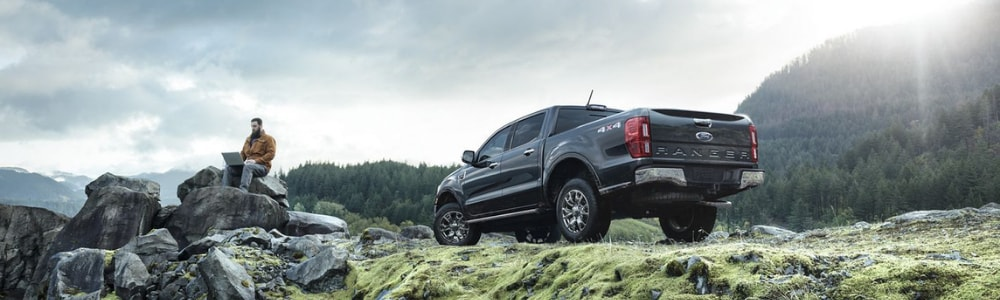 A sky cam view of a grey 2019 Ford Ranger truck parked on the side of a grassy cliff with the driver sitting on a rock formation as the sun glares over a mountain top in the distance