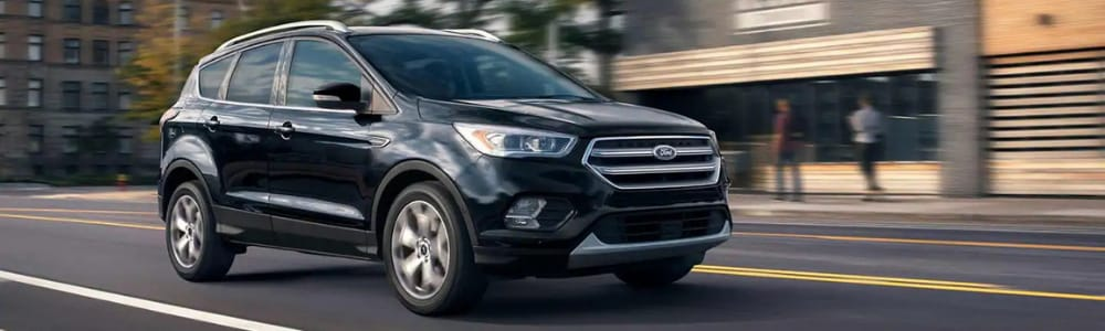 Passenger side view of a black 2019 Ford Escape driving down a city street in Colorado Springs