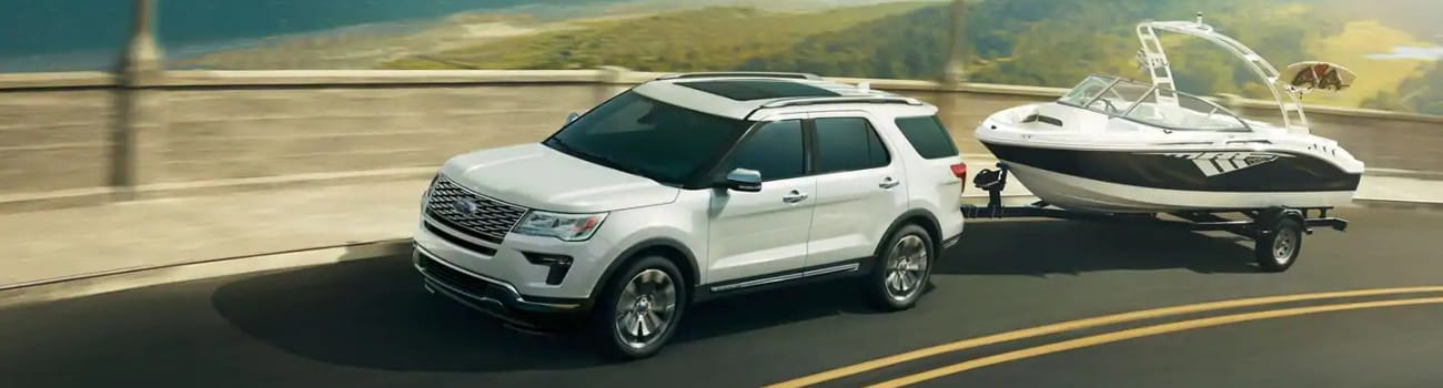 Aerial driver side view of a white 2019 Ford Explorer in Colorado Springs towing a boat as the Ford SUV drives down the highway