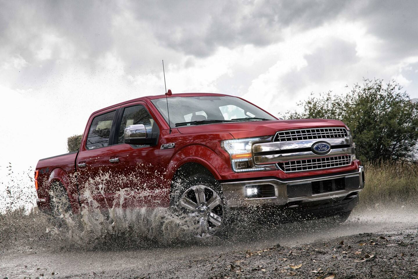 A red 2020 Ford F-150 driving through mud and splattering it everywhere