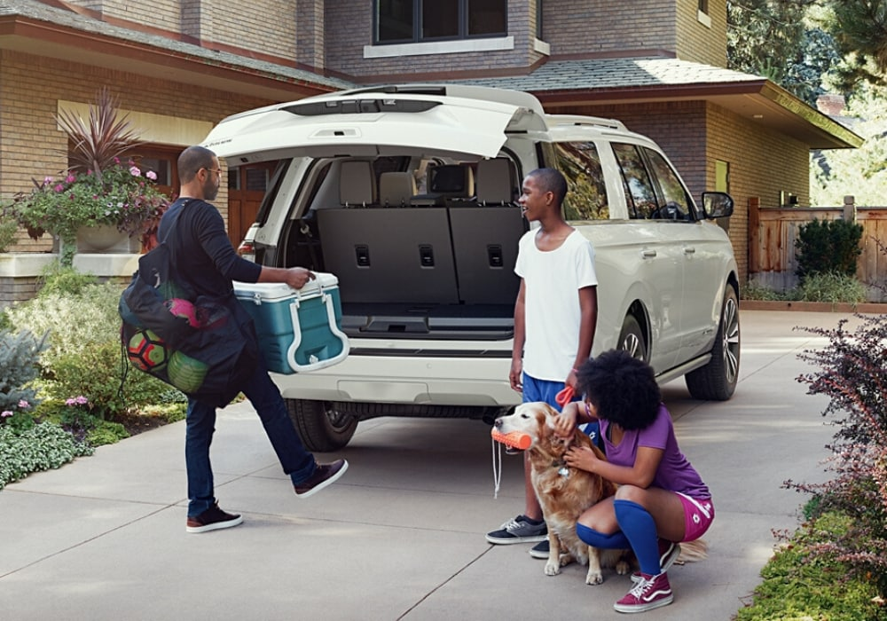 Happy family loading cargo into the spacious interior of a 2020 Ford Expedition ready for vacation