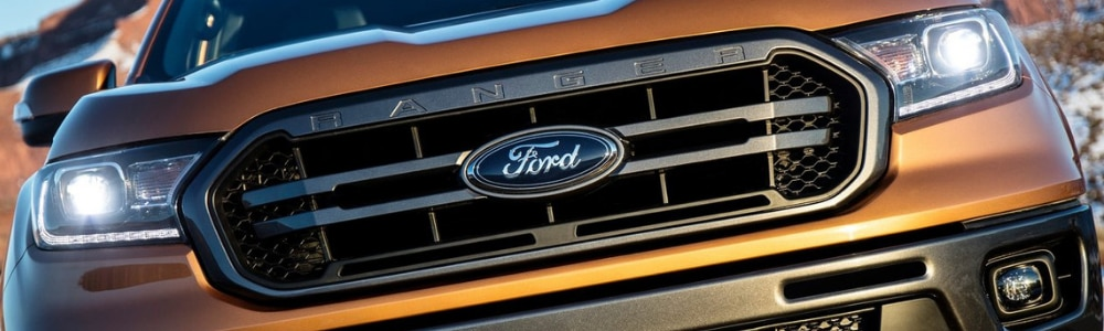 Close up view of the grill of an orange 2019 Ford Ranger truck with headlights glaring into the camera lens