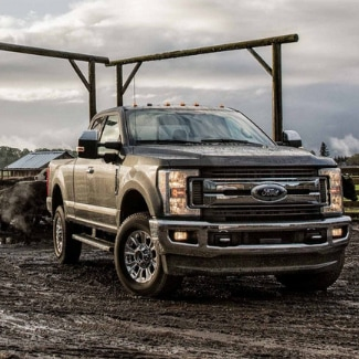 A dark grey 2019 Ford Super Duty pulling out of a gate driving through the mud at a farm with cows in the background