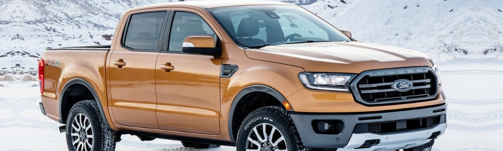 Passenger side angle of an orange 2019 Ford Ranger truck parked in the snow at the base of a snowy mountain range