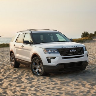 A white 2019 Ford Explorer parked in the sand on a beach with a background view of the ocean with a seagull flying by