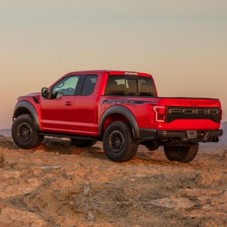 A red 2019 Ford F-150 pulled up to the edge of a rocky desert cliff with an orange hazy sky in the background