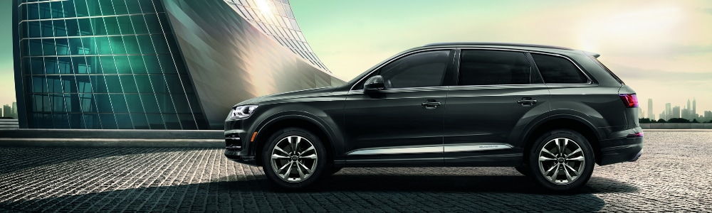 Driver side view of a metallic grey 2019 Audi Q7 SUV parked on bricked concrete path outside of a sleek modern building with many windows
