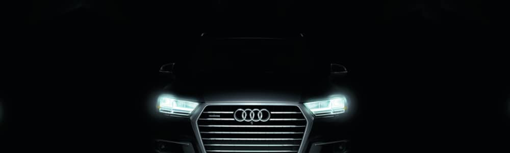 Angle of the front of a 2019 Audi Q7 SUV in a dark tunnel with the bright LED headlights shining showing the visible Audi logo on the grill