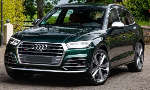 2020 Audi SQ5 green parked cobblestone wall barrier garden forest