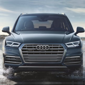 The front view of a grey blue 2019 Audi Q5 driving through a puddle in the day time with a partly cloudy sky in the background
