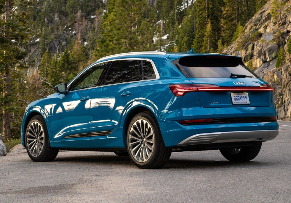 Rear exterior view of a blue 2020 Audi e-tron SUV parked at an overlook on a mountain side