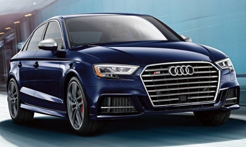 2020 Audi S3 dark blue driving by a shaded city building