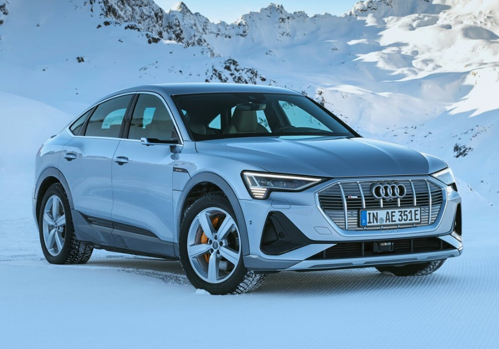 Front exterior view of the new Audi e-tron Sportback parked in the snow atop a snow-packed mountain range