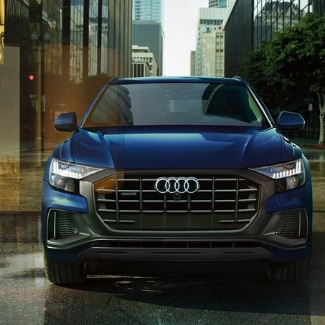 Front view of a blue 2019 Audi Q8 crossing an intersection on a busy city street with blurred cars and city reflections off glass windows of skyscrapers in the background