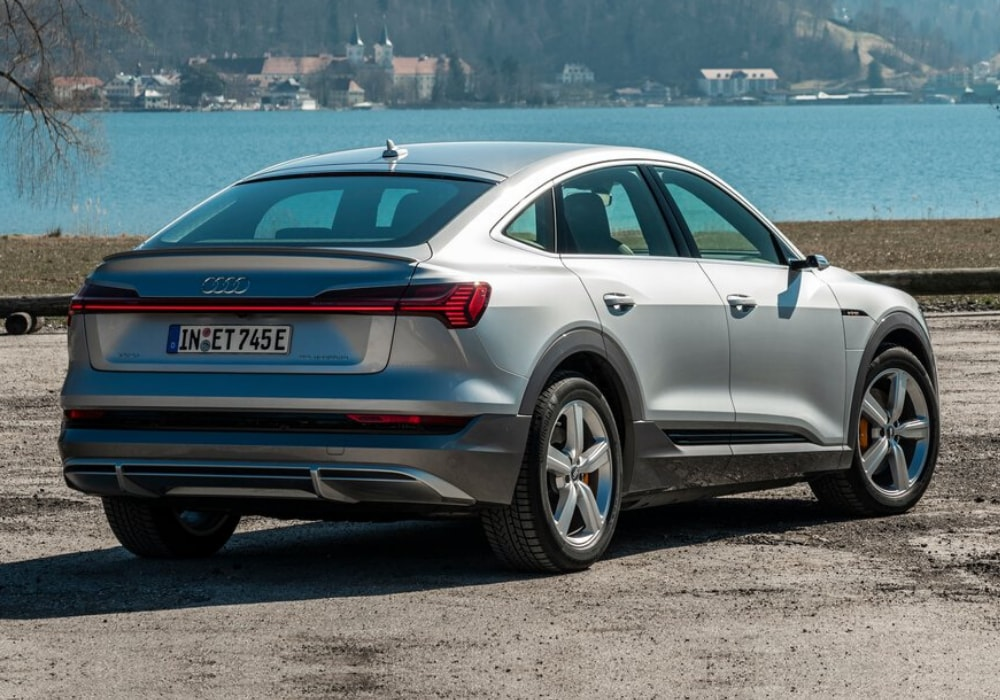 2020 Audi e-tron Sportback rear exterior design view parked in front of a lake