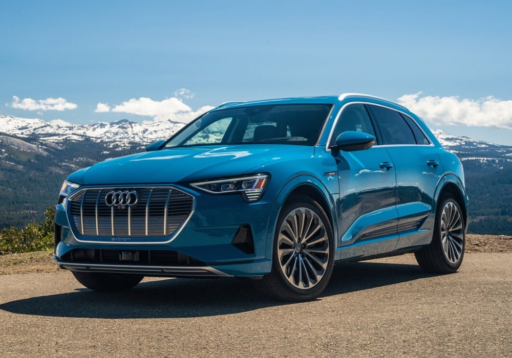 2020 Audi e-tron SUV in blue color parked on a mountain-side cliff with a snowy mountain range in the distance