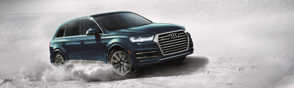 Front passenger side angle of a galaxy blue 2019 Audi Q7 SUV driving through heavy snow with clouds of snow kicking out from the spinning tires