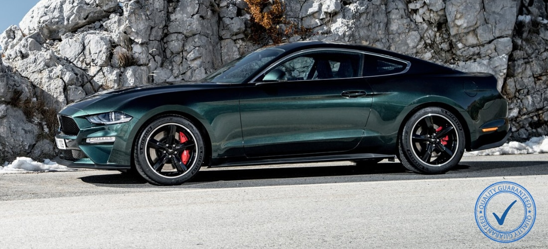 Ford Mustang Bullitt parked on a Rocky Mountain road with a stamp of approved quality