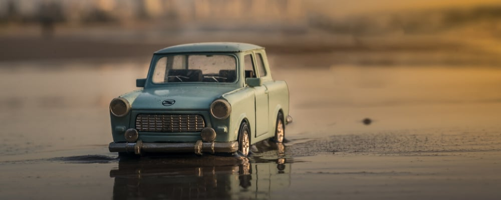 Miniature toy car model stuck in wet sand on the shore of a beach