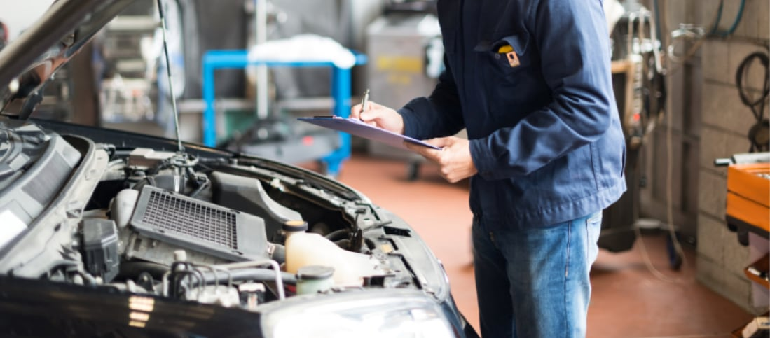 Auto mechanic performing an inspection on a used car