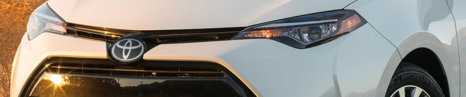 Close up angle of the front grille on a white used Toyota Corolla as the sun glares of the front bumper