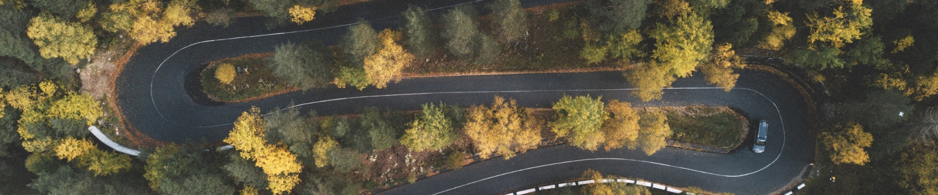 Aerial view of a used car as it drives down a winding curvy road through a forest