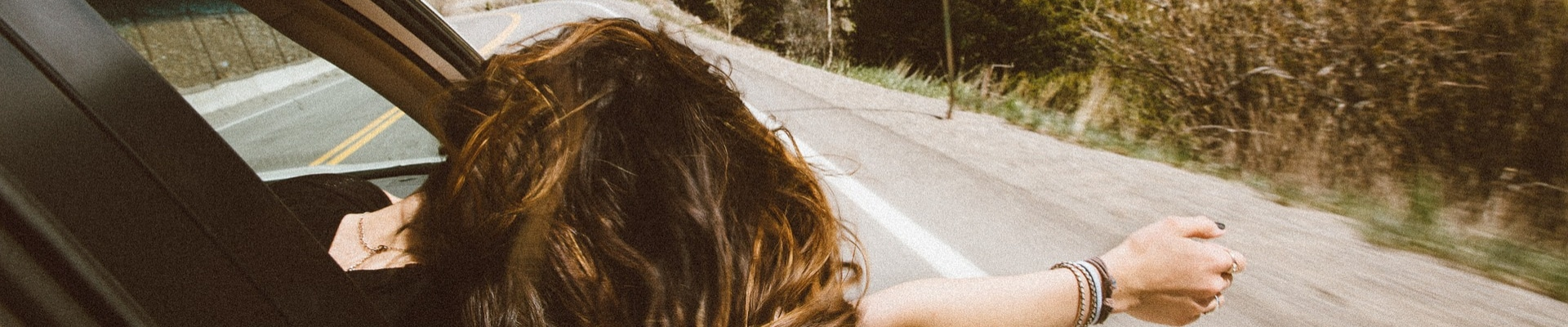 Young woman in the passenger seat hanging her arm and head out of the window enjoying the ride as the breezy air blows through her hair