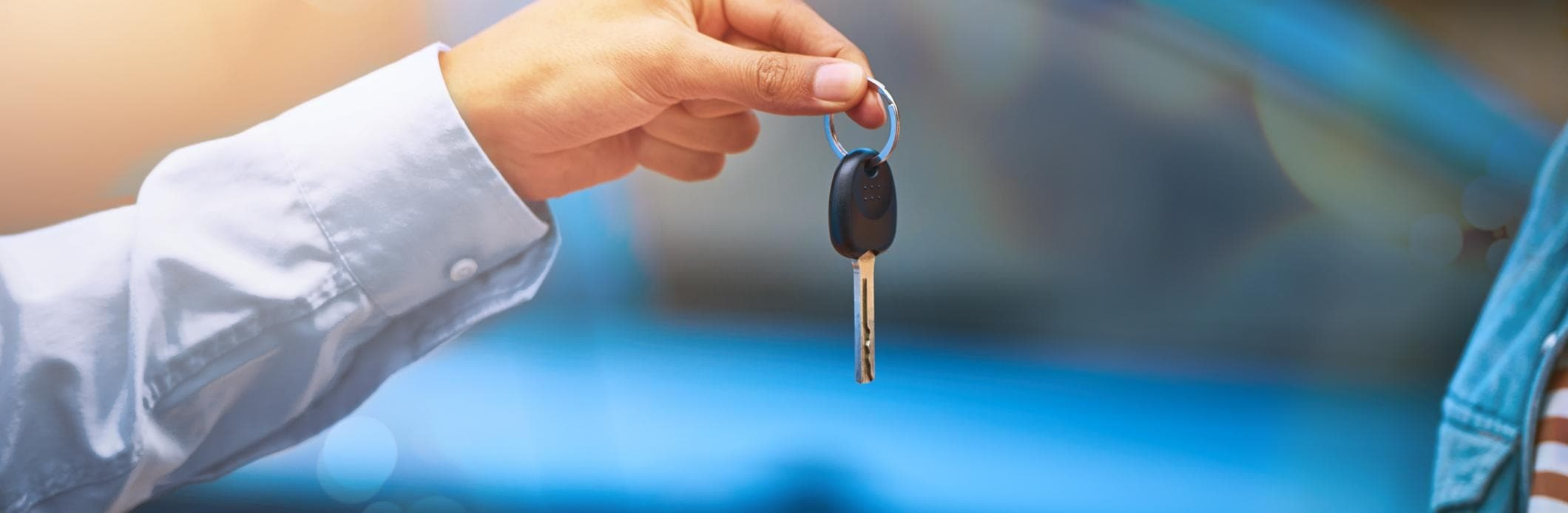 A car salesman handing the keys of a newly purchased car over the the new owner