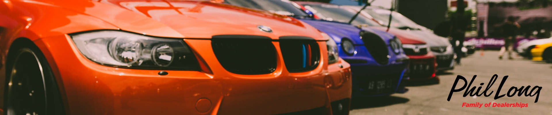 Close up view of an orange used BMW car at the front of a line of used cars on display