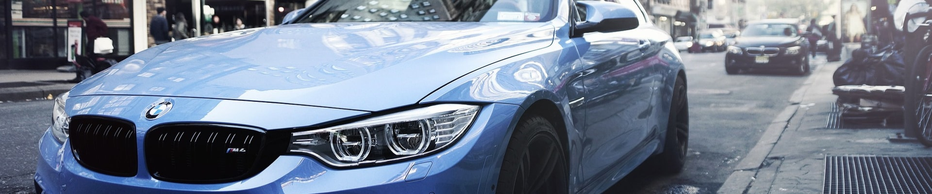 Close up look at the front exterior of a used blue BMW M6 car parked on a busy city street