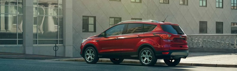 Driver side shot of a red 2019 Ford Escape driving down an empty city street with a tall modern building in the background