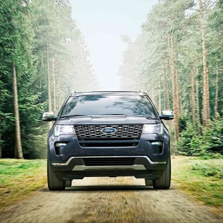 The front view of a dark blue 2019 Ford Explorer driving down a dirt path splitting the tall green forest in the background