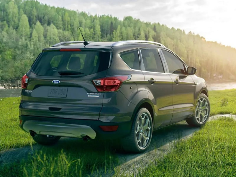 Back Side Exterior of a dark green 2019 Ford Escape parked on grassy knoll by a river