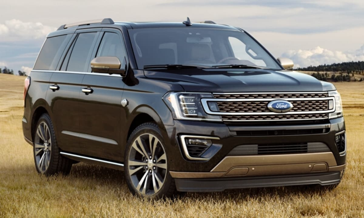 New Ford Expedition parked in a grass field on some hills before a mountain range