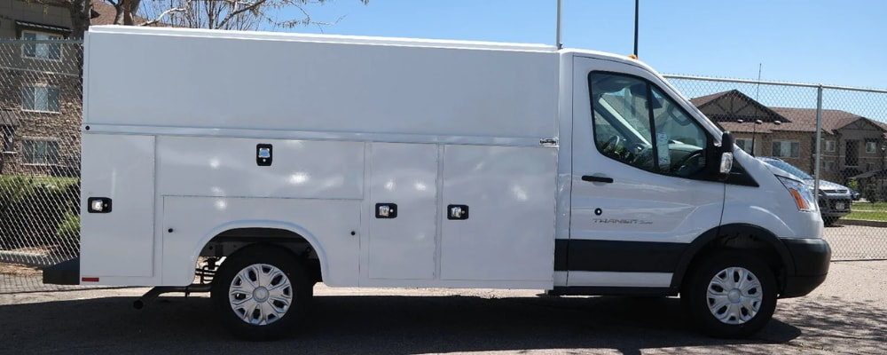 Passenger side of a new Ford commercial work van for sale in Denver at Phil Long Ford