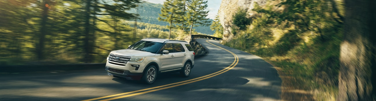 A white 2019 Ford Explorer driving down a curvy road around the edge of a mountain side through a green forest