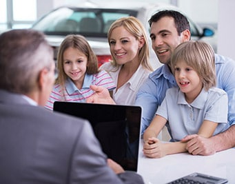 A family sitting at a Ford dealership in Denver buying a new car from Phil Long Ford