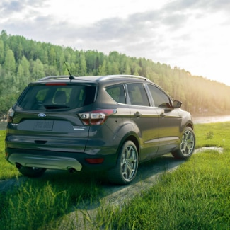 A look at the back side view of a steel green 2019 Ford Escape parked on a grassy knoll overlooking a river that runs by the entrance of thick green forest