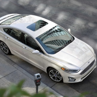 An aerial view of a white 2019 Ford Fusion parked on the side of a street with a parking meter and blurred tree leaves in foreground