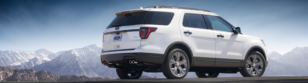 Passenger side view of a white 2019 Ford Explorer parked at the edge of a cliff overlooking a snowing mountain range
