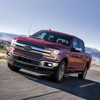 A ruby red 2019 Ford F-150 driving down an open country road with a small beautiful mountain range in the background
