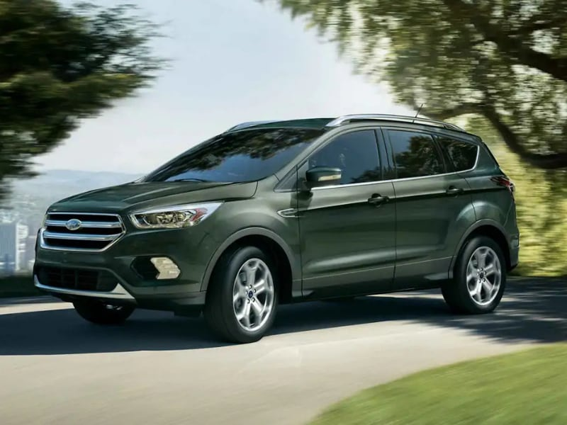 Front Side Exterior of a dark green 2019 Ford Escape driving around a curve through some trees