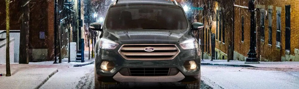 Front view of a dark green 2019 Ford Escape driving on an uphill city street in Denver through the snow with ease