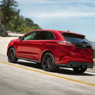 A red 2019 Ford Edge driving on a curvy road with a green forest on the left overlooking a bay of water on the right