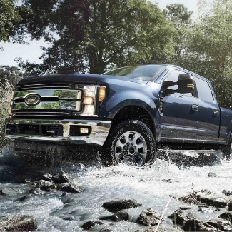 A front side view of a dark steel blue 2019 Ford Super Duty driving through a rocky creek with water splashing onto the grill and undercarriage with lush green trees in the background