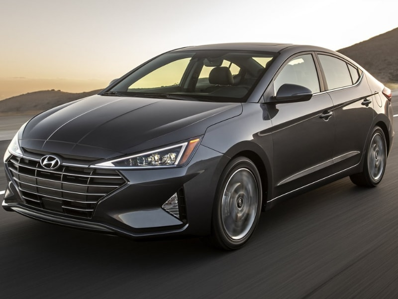 Front driver side exterior of a 2019 Hyundai Elantra driving down a country road