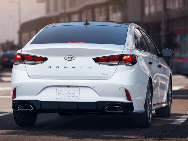Back side Exterior of a white 2019 Hyundai Sonata waiting at a stoplight intersection
